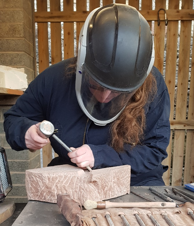 A stonemason in protective gear using hand tools to work on a stone carving