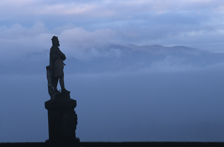 Atmospheric photo of a statue of Robert the Bruce silhouetted against misty mountains
