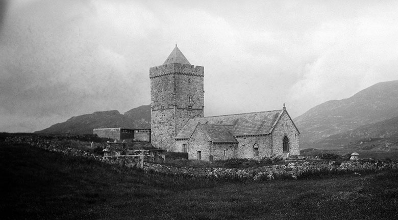 View of a plain church surrounded by a hilly landscape.
