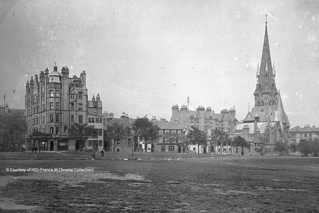 From Bruntsfield Links, view of a church with a large spire and tenement buildings.