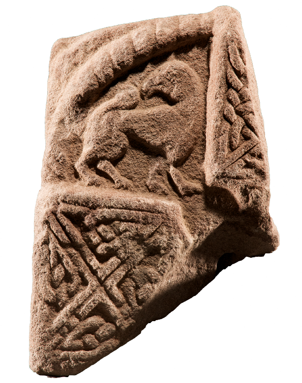 Close up photo of one of the St Vigeans Pictish stone with carvings of ornate patterns and a griffin looking over its shoulder