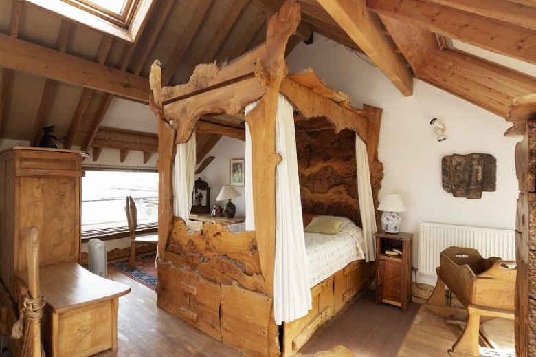 A large four-poster bed carved entirely from wood in one of the bedrooms at The Steading