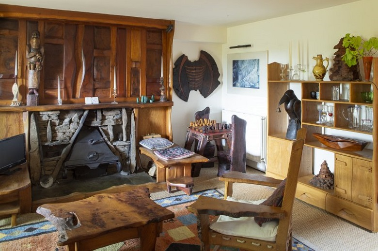 A living room inside The Steading full of wooden furniture and furnishing. An intricately carved figure features above the fireplace.
