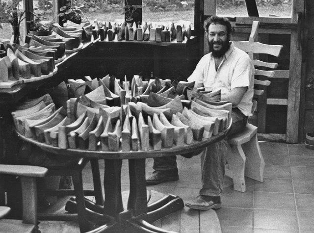 Black and white photo of an artist sitting at a round wooden table which is covered in a large selection of carved wooden axes