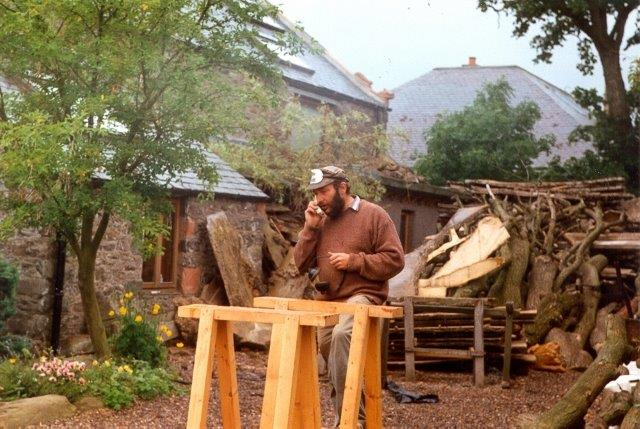 An artist working with wood outside his house. Trees, flowers and a large pile of timber can be seen behind him.