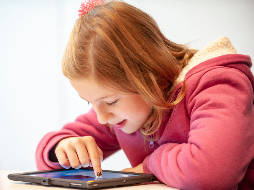 A girl in a pink jacket smiling as she uses a tablet