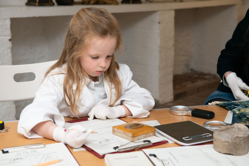 A girl in a white coat and wearing white gloves looks at an object in front of her as she holds a pencil