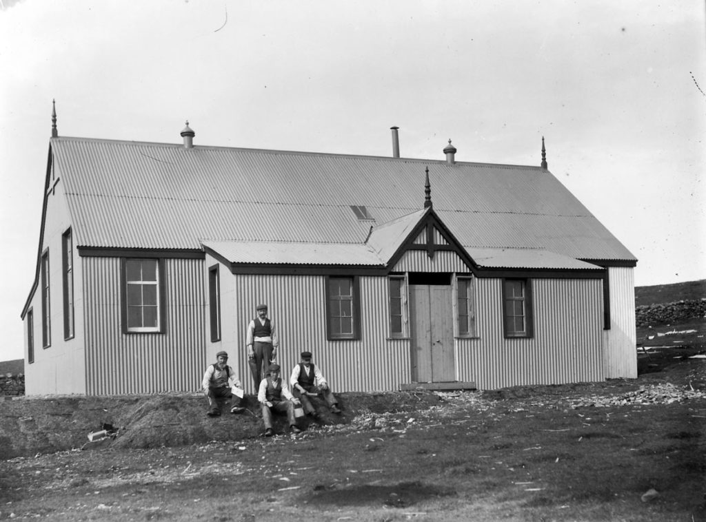 A black and white photograph of four people sitting outside a corrugated iron building