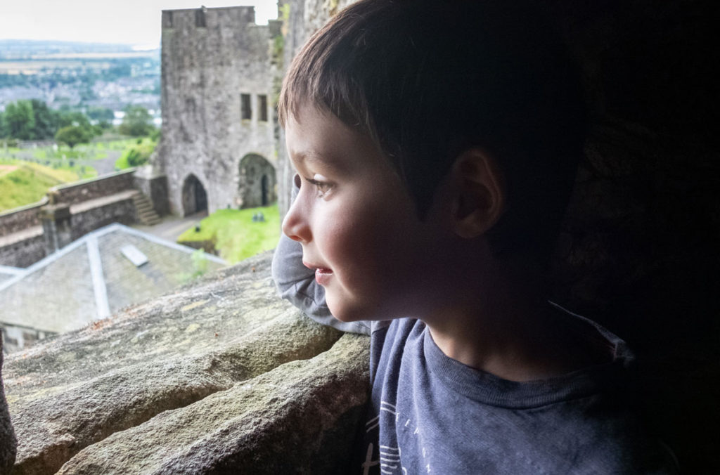 A young boy looks out of a window at a partially ruined castle