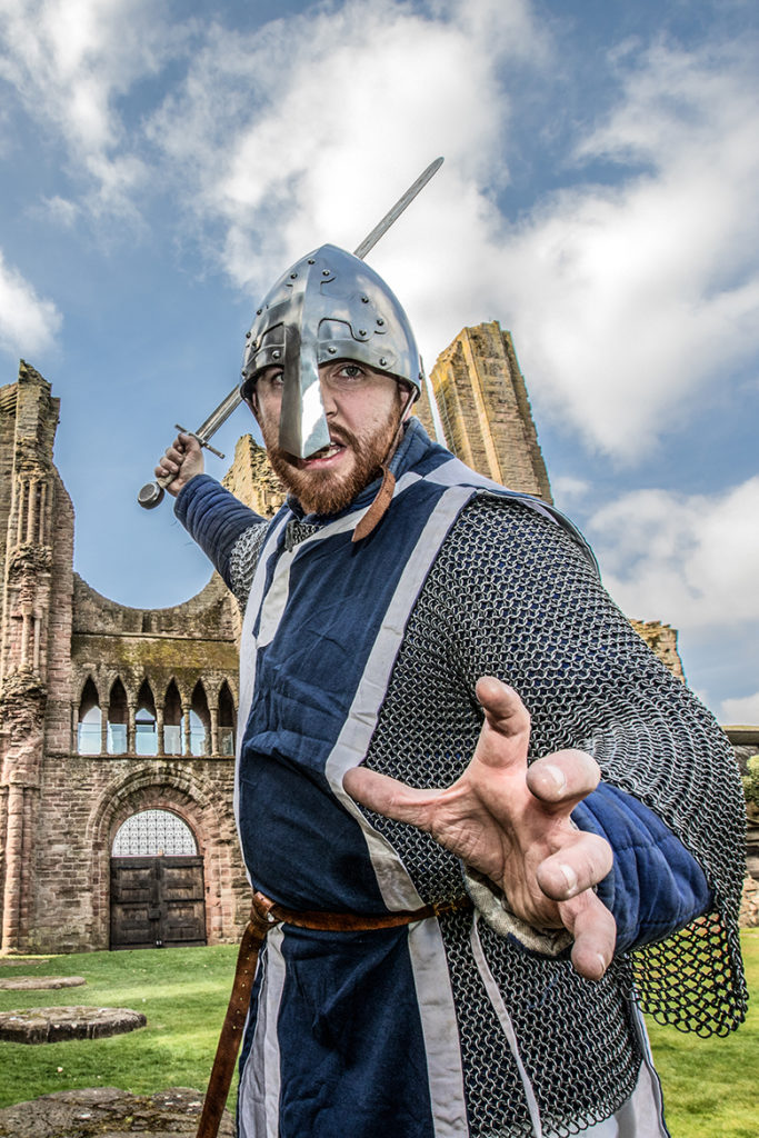 A man in medieval costume wields a sword in front on Arbroath Abbey.