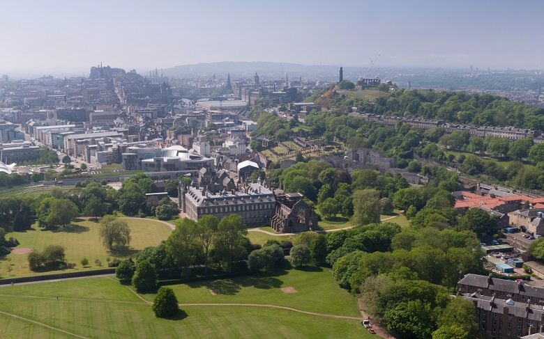An aerial photo of Holyrood Palace, Holyrood Park and the city of Edinburgh taken by drone.