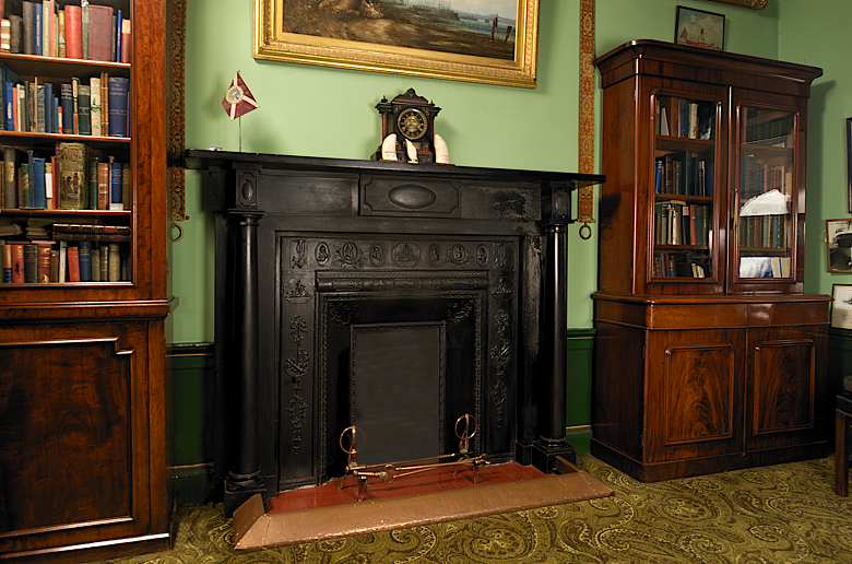 A large, black, Georgian fireplace flanked by two glass fronted book cases.