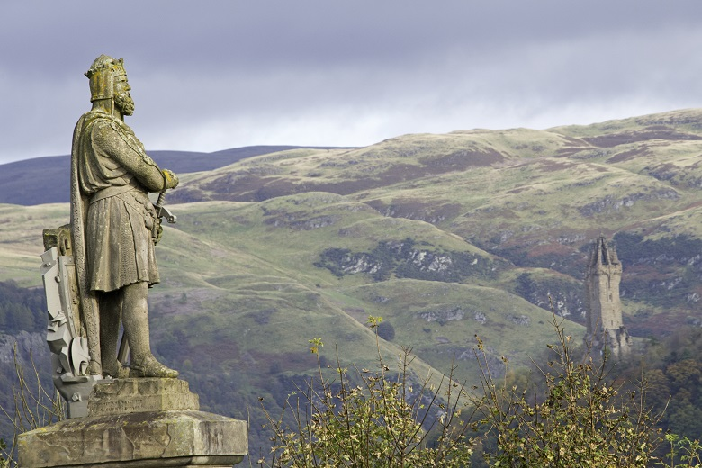 A statue of Robert the Bruce on the esplanade at Stirling Castle with the Wallace Monument and the hills outside Stirling