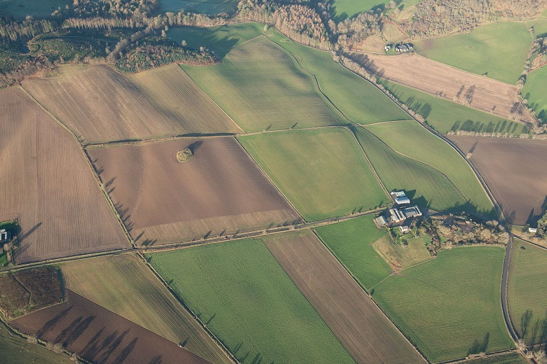 An aerial photo of a burial cairn surrounded by farmland
