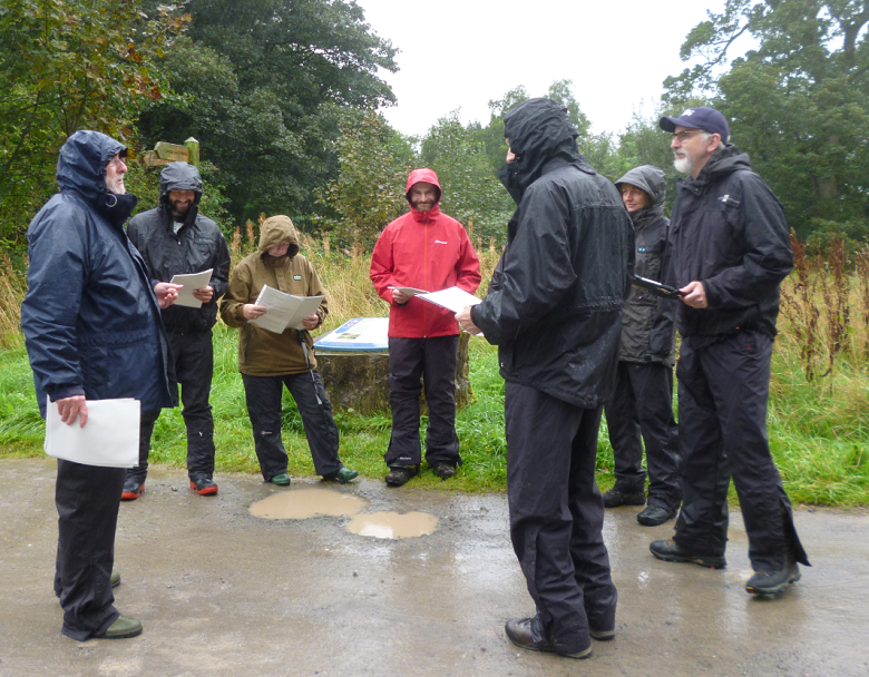 A group of filed officers wearing raincoats engaged in a training session