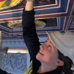 A woman wearing a hard hat works on a painted ceiling.
