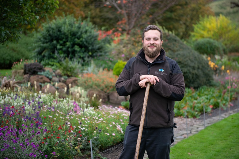 A gardener in HES branded clothing poses with a rake