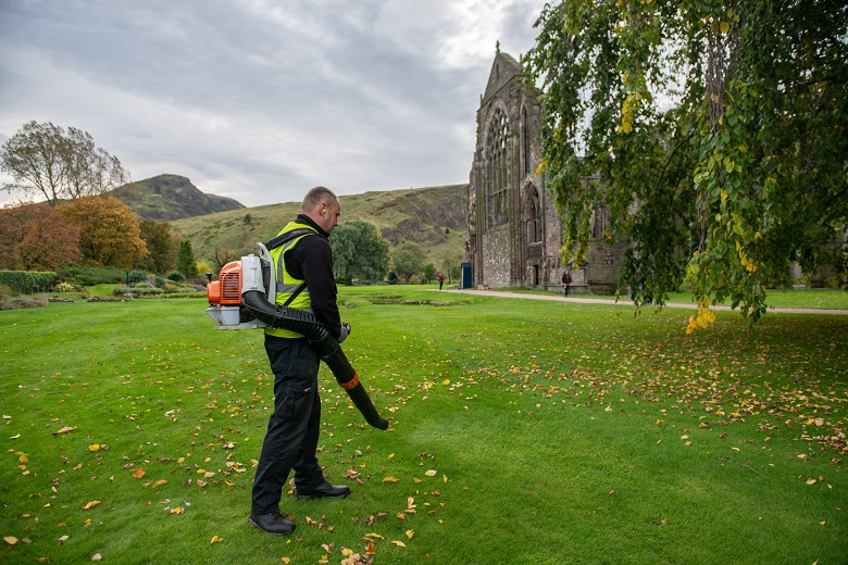 A gardener works with a leaf blower in the shadow of Holyrood Abbey