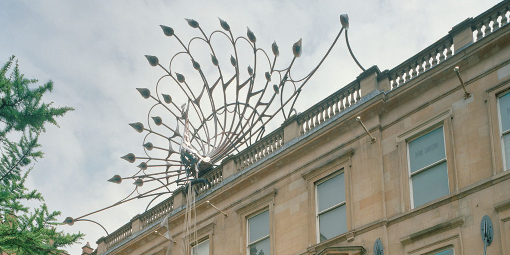 large metal peacock on top of a long tenement building