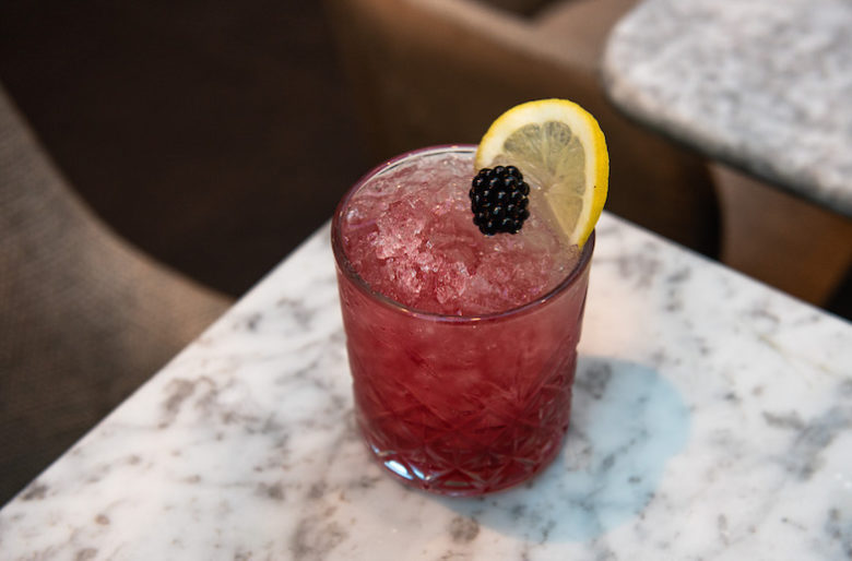 a purple cocktail in a highball glass topped with a blackberry and a slice of lemon.