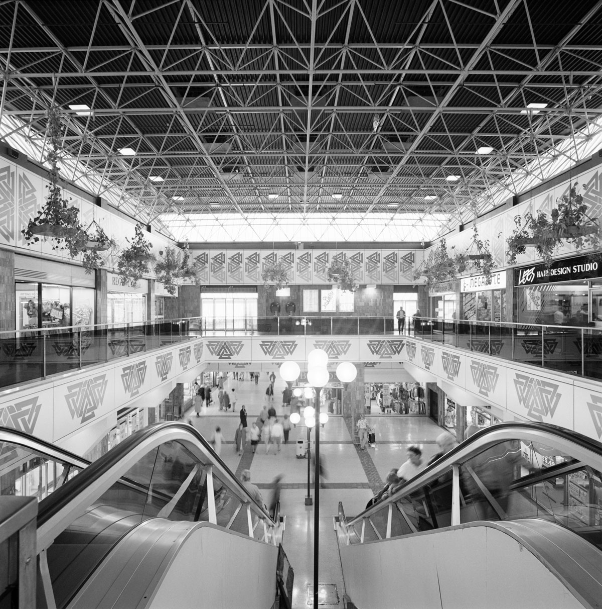 Black and white view looking down from the top of an escalator showing a Postmodern shopping centre with open ceiling structure and geometric decorative panels