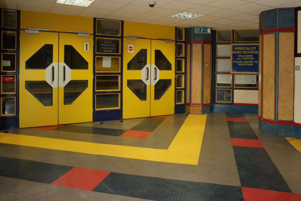 The brightly coloured interior of a high school, with yellow doors and a patterned floor