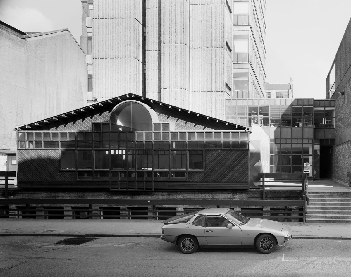 black and white image of a shed like building with sloping roof and several windows, with a concrete tower in the background and two door car parked in front