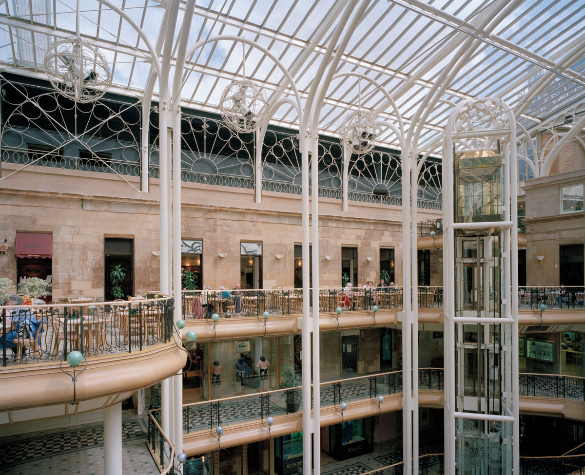 section of a multi story shopping centre with glass ceiling and ornate ironwork