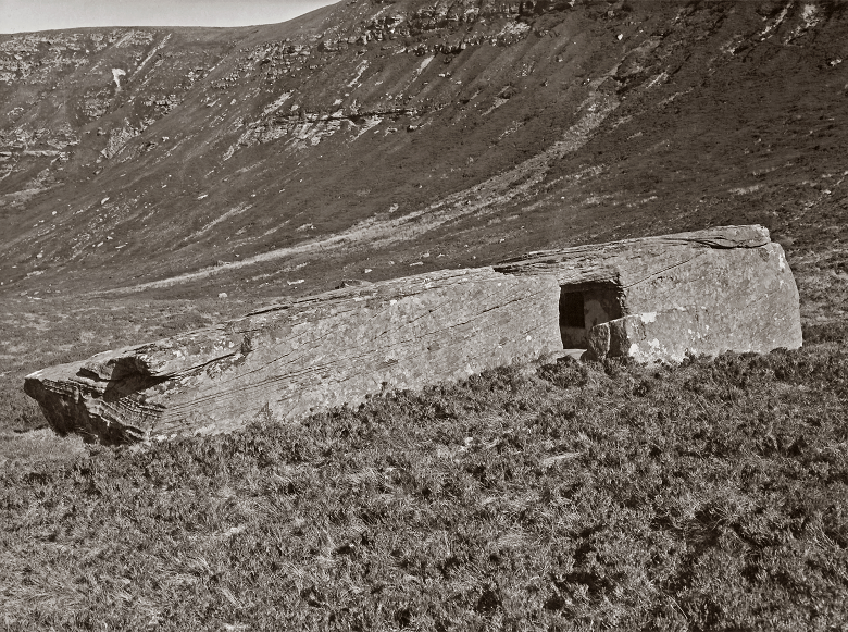 A black and white photo of a large hollowed-out stone in a remote glen