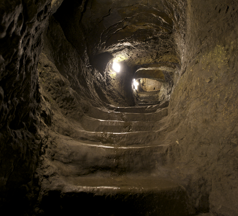 A dark tunnel with rough walls. Uneven steps ascend.
