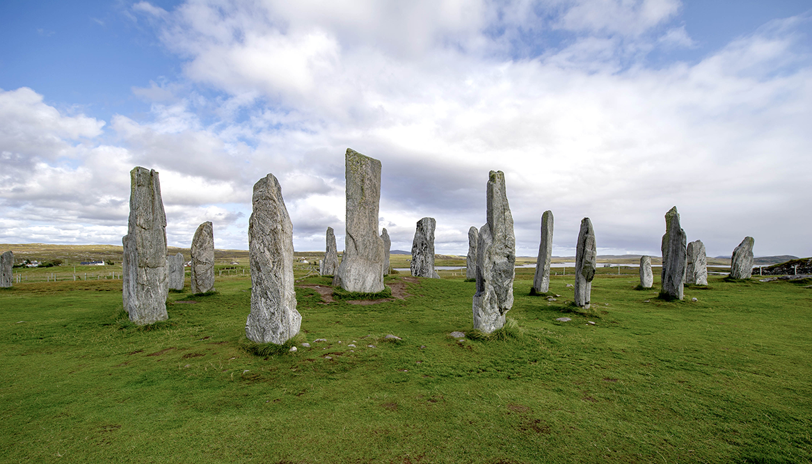 a line of standing stones on green grass