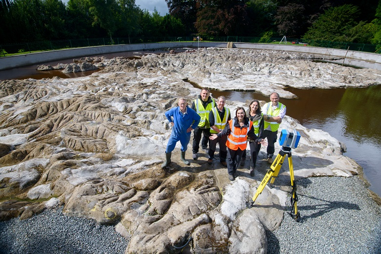A team of HES staff working with a camera and a tripod on a large 3D map of Scotland