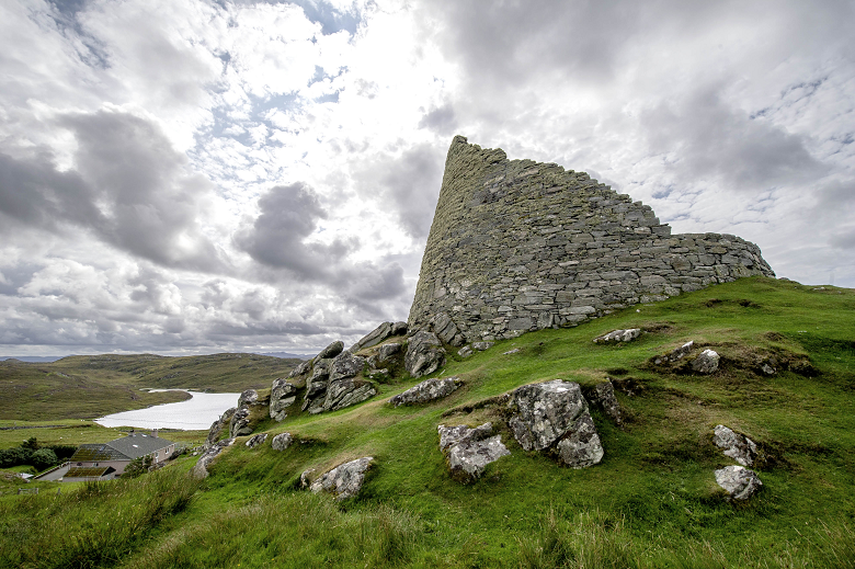 A close up shot of a dry stone broch on a grassy and rocky mound