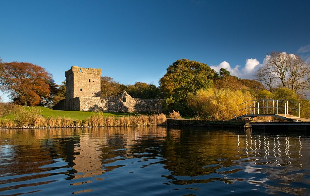 Lochleven Castle pictured from a boat arriving at a small pier