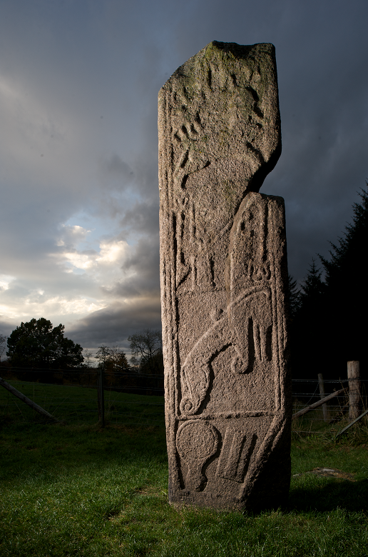 A Pictish stone photographed at dusk featuring stone carvings of animals and beasts