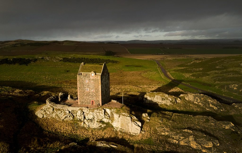 A drone photo of a fortified tower house under atmospheric skies