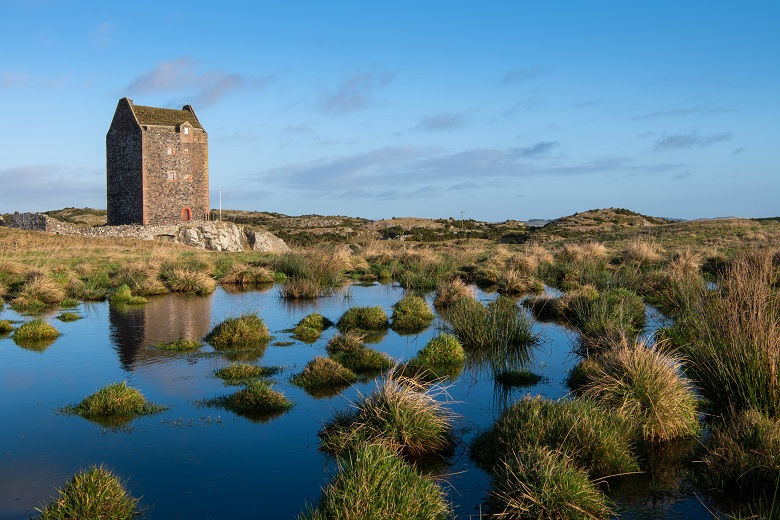 A small pond in front of a fortified tower house in winter sunshine.