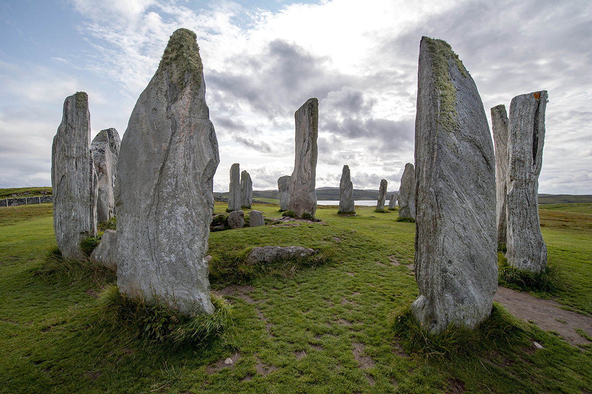 view of Calanais Standing Stones, a circle of tall grey stones of different sizes on green grass with cloudy sky above