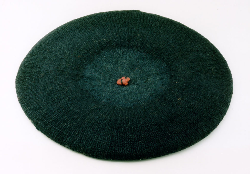 A top-down view of a bonnet hat with an orange knot in the centre.