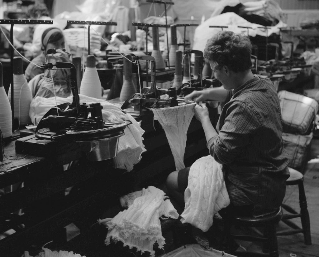 A black and white photograph of a woman working on a knitting machine