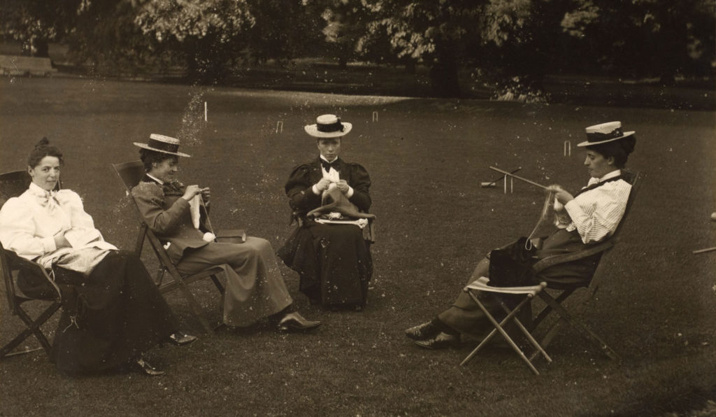 A black and white photo of four women knitting on a croquet lawn in Edwardian dresses.