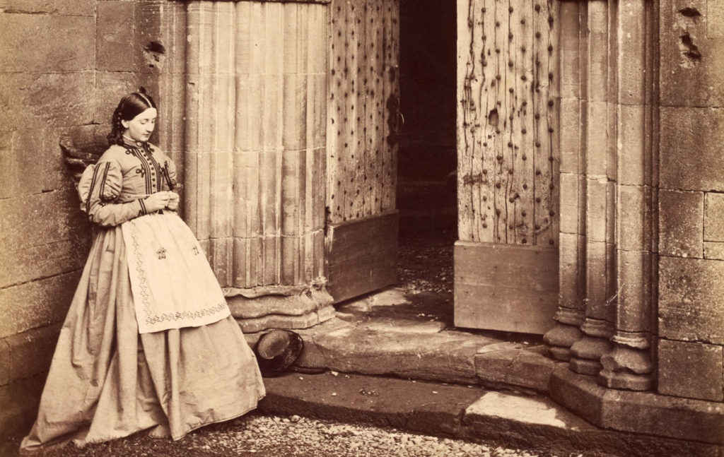 A black and white photograph of a woman standing beside an ornate doorway, knitting.