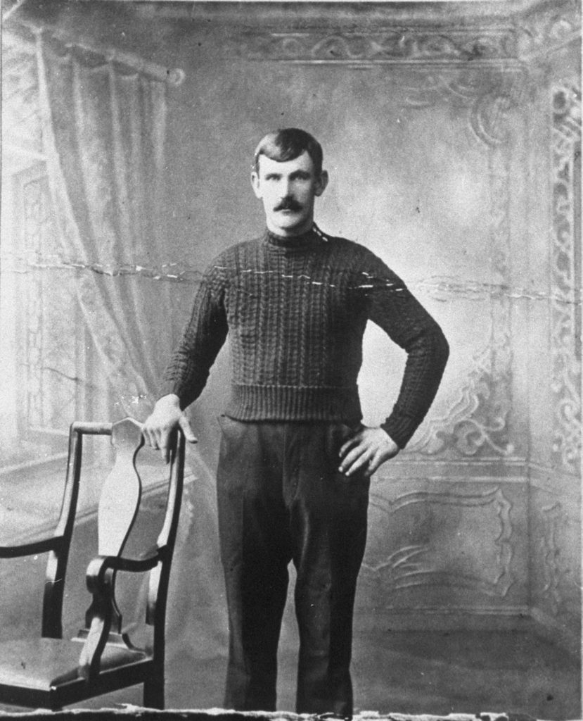 A black and white photograph of a man with a mustache wearing a thick woolen jumper.