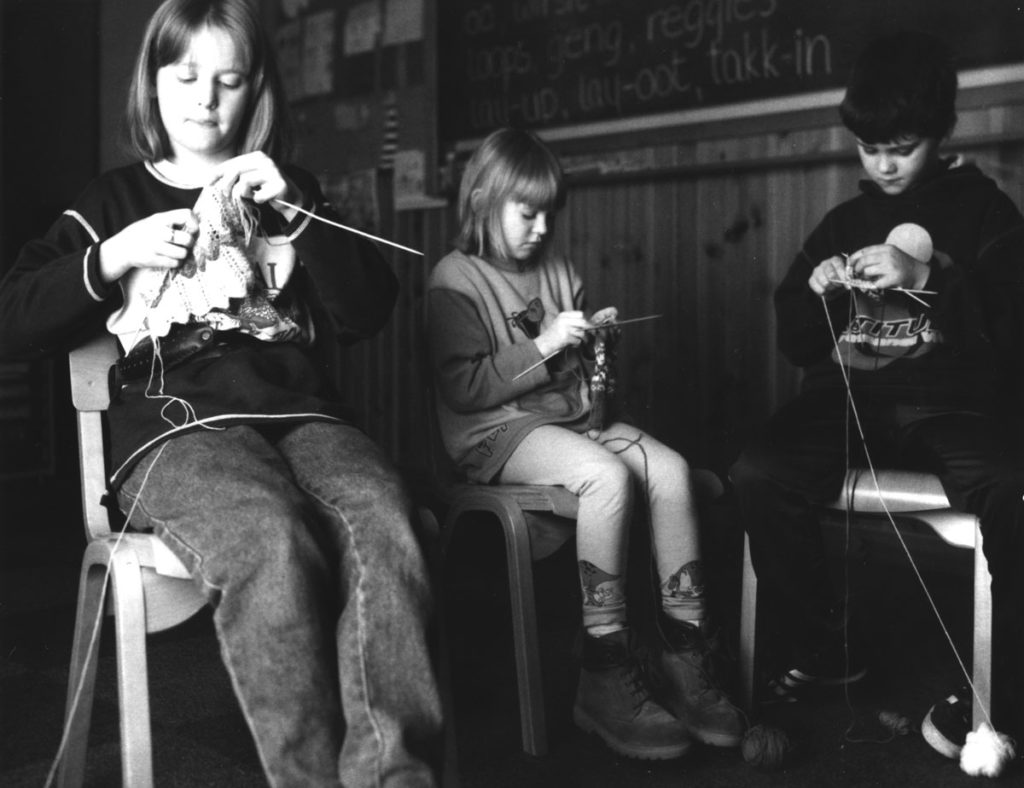 Three children sit on chairs, concentrating on the knitting task in front of them.