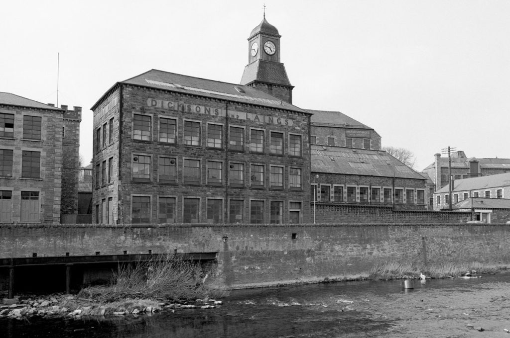 Black and white photograph of a large factory building beside a river