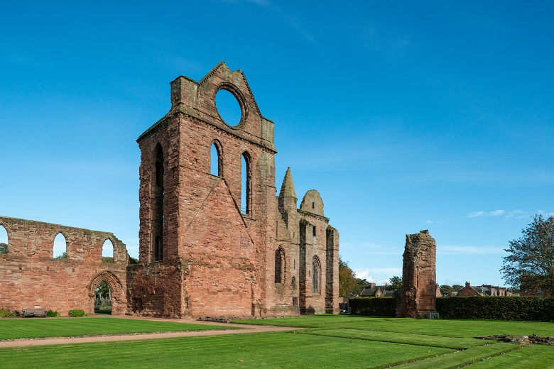 The ruins of Arbroath Abbey including a distinctive round window under a clear blue sky