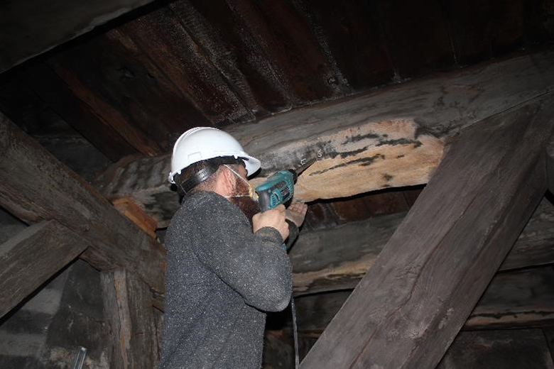 A man in a hard hat drills into an old timber.