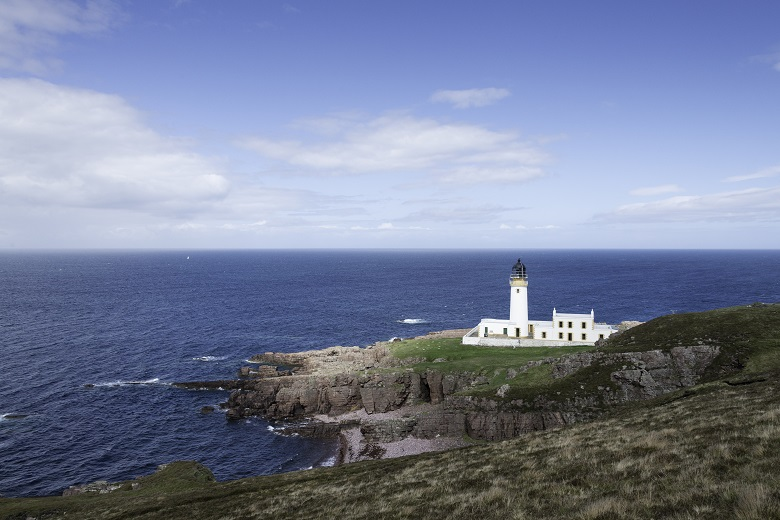 A white lighthouse over looking the sea at the Minch, Scotland