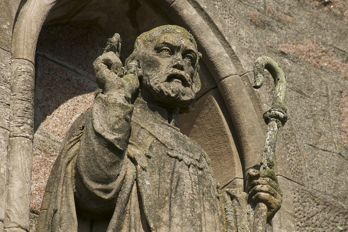 carved figure of a bearded man in a robe with one hand in the air and the other holding a crook