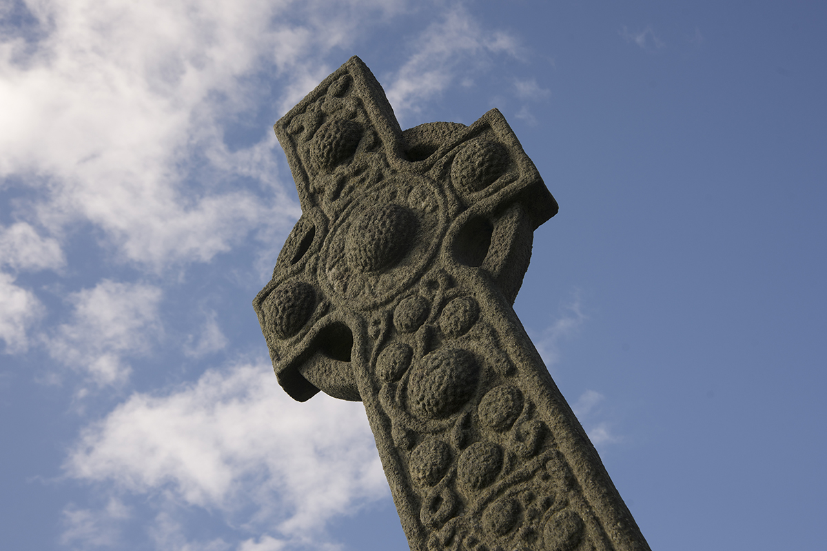 carved stone cross with blue sky behind it